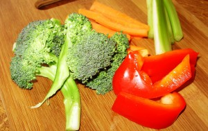 Fresh broccoli, red pepper and celery on a cutting board